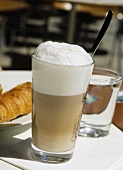 Latte macchiato, a glass of water and croissant