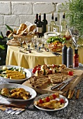Various barbecued dishes in front of table laid for party