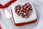White cake with raspberry heart, cake slice beside it