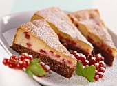 Three pieces of black and white cake with redcurrants