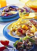 Shrimp salad, chicken kebab with pasta, fish soup behind