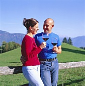 Young couple drinking wine against the Dolomites, S. Tyrol