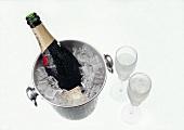 Bottle of Moet & Chandon in cooler beside two full glasses