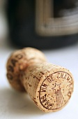 A champagne cork in front of champagne bottle