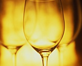 Several empty glasses side by side in yellow light