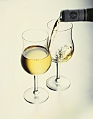Pouring white wine into a glass, filled glass in front
