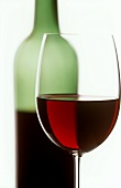 Red wine glass with half-full wine bottle in background