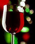 Rotwein im Glas, farbige Lichtreflexe im Hintergrund