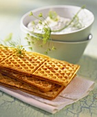 Tasty cheese waffles and a bowl of quark with dill