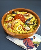 Paella in brown stoneware dish, Spanish postcard beside it