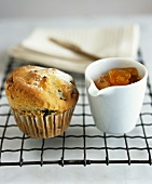 Fruit muffin and a pot of apricot jam