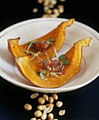 Baked pumpkin wedges with peanut and garlic dressing