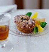 Sweet spiced bun with citrus fruit wedges on glass plate