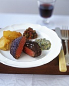 Beef steak with baked potato wedges and two sauces