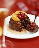 Christmas pudding, decorated with clementine and cranberries