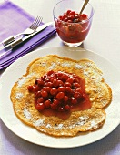 Walnut pancake with icing sugar and cranberry compote