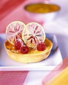 Lemon tartlet garnished with lemon slices and raspberries