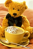 A cup of hot chocolate with cream, teddy behind