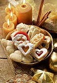 Assorted Christmas biscuits in a bowl; candles