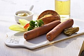 Two sausages on chopping board; lettuce garnish, roll, mustard