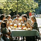 Young people with beer and Bavarian snacks in beer garden