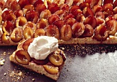 Tray-baked plum cake; one piece with whipped cream