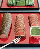 Roast beef in herb coating and a bowl of pesto
