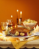Roast goose with red cabbage and apple on festive table