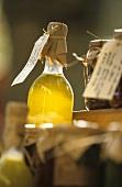 Bottle of olive oil sticking up above jars of preserves