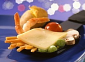 A raclette pan with raw vegetables, shrimps & cheese