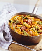 Potato and bean goulash with sliced sausages