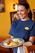 Junge Frau serviert Teller mit Enchiladas