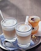 Two glasses of latte macchiato and muffins on a tray