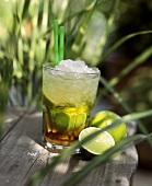 Glas Caipirinha auf einem Holztisch im Freien