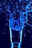 Blaues Wasser spritzt aus Wasserglas