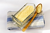 Polenta meal in glass container and on a spoon