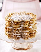 Dusting butter waffles with icing sugar