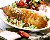 Fish in pastry casing on green salad with mushrooms