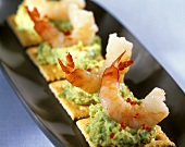 Cracker with avocado puree and shrimp tails