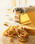 Home-made wholemeal tagliatelle in front of pasta maker
