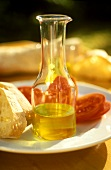 Small glass bottle of olive oil, tomatoes and bread beside it