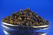 Black peppercorns in a glass bowl