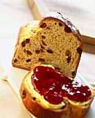 Piece of raisin bread and slice with butter and jam