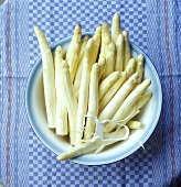 White asparagus in a dish on a kitchen towel