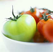 Green tomato with red tomatoes in a bowl