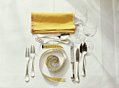 Picture symbolising diet: laid table with tape measure