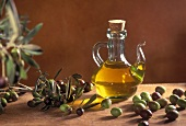 Olive oil in a small glass carafe with olives