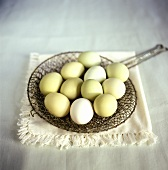 Still life with green hen's eggs on metal strainer