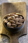 Terracotta bowl of salted almonds on a wooden board