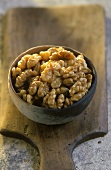 Terracotta bowl of walnut kernels on a wooden board